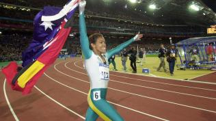 (RUN219) 25th September, 2000. Sydney Olympic Games. Athletics at Stadium Australia. Womens 400m Final. Australia's Cathy Freeman walks a lap of honour, carrying the Australian and Aboriginal Flags, after winning Gold in the Womens 400m Finals. (AAP PHOTO/Dean Lewins).